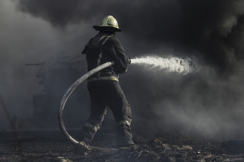 A fireman surrounded with smoke extinguishing a fire