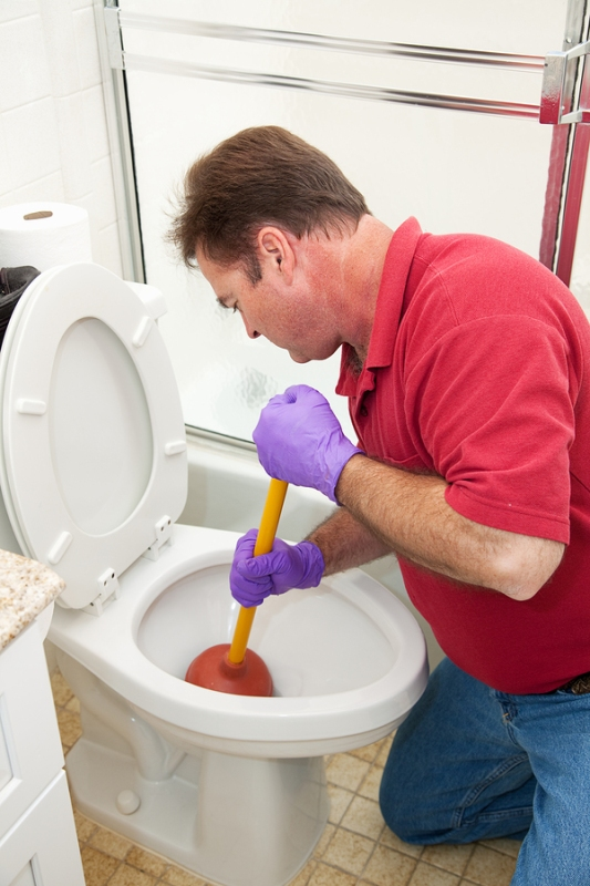 A plumber fixing a clogged toilet