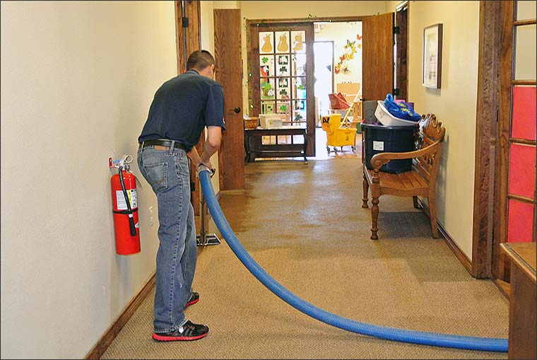 worker cleaning, drying and decontaminating carpet