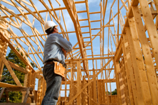 a man in a hard hat looks over the wood framing of a building under construction